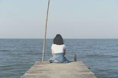 La mujer se está sentando solamente en concepto de la libertad del puente con el cielo azul fotografía de archivo