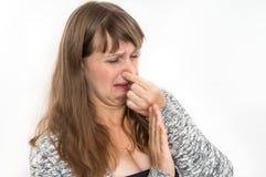 La mujer se está sosteniendo la nariz - concepto del mún olor foto de archivo