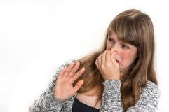 La mujer se está sosteniendo la nariz - concepto del mún olor fotografía de archivo