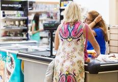 La mujer se está colocando en la caja registradora y está pagando las mercancías Fotografía de archivo libre de regalías