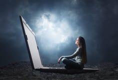 La mujer se está sentando en un ordenador portátil grande Imágenes de archivo libres de regalías