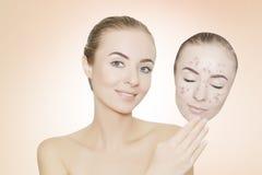 La mujer se lleva la máscara con el acné y las espinillas, fondo rosado Fotografía de archivo