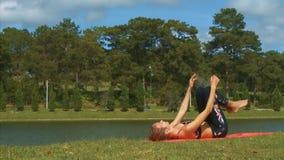 La mujer se opone en actitud de la yoga en hierba a las plantas