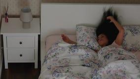 La mujer se prepara se va a la cama y duerme y apaga el soporte de la noche además de la cama almacen de metraje de vídeo