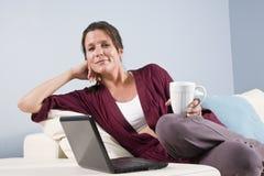 La mujer se relajó en el sofá con la taza de la computadora portátil y de café fotografía de archivo libre de regalías