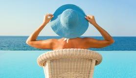 La mujer se relaja cerca de piscina del infinito en día asoleado Imagenes de archivo