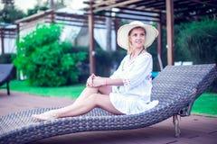 La mujer se relaja cerca de sunbath de la piscina en el complejo playero en th fotografía de archivo