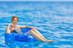 La mujer se relaja en el anillo inflable en agua de mar fotos de archivo