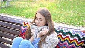 La mujer se relaja en el banco en parque verde hermoso movimiento video 4K la muchacha atractiva se sienta en un banco de madera  almacen de video