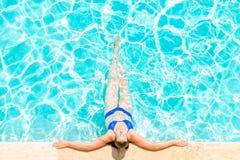 La mujer se relaja en el borde de la piscina Imágenes de archivo libres de regalías