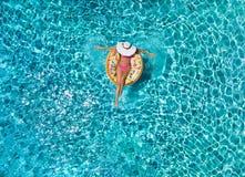 La mujer se relaja en un flotador en forma de anillo sobre el agua azul, chispeante de la piscina fotos de archivo