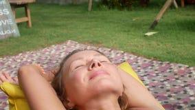 La mujer se relaja en una bolso-silla en un claro con la hierba verde almacen de video