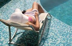 La mujer se relaja por la piscina Fotografía de archivo libre de regalías