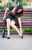 La mujer se sentó en el banco porque sus piernas lastimaron Foto de archivo libre de regalías