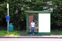 La mujer se sentó en una parada de omnibus al lado de la cartelera en blanco Imagen de archivo libre de regalías