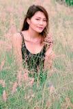 La mujer se sentaba en el prado en una atmósfera hermosa foto de archivo libre de regalías
