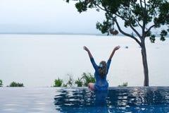 La mujer se sienta, aumentando sus manos, al borde de la piscina foto de archivo