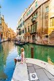 La mujer se sienta cerca de un canal y las góndolas admiran en Venecia Fotos de archivo