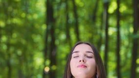 La mujer se sienta con los ojos cerrados disfrutando del momento, naturaleza feliz de los sentidos de la señora profundamente almacen de metraje de vídeo