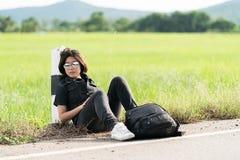 La mujer se sienta con la mochila que hace autostop a lo largo de un camino Fotografía de archivo