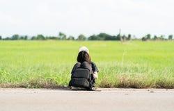 La mujer se sienta con la mochila que hace autostop a lo largo de un camino Fotos de archivo