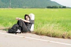 La mujer se sienta con la mochila que hace autostop a lo largo de un camino Imagen de archivo libre de regalías