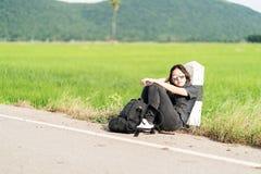La mujer se sienta con la mochila que hace autostop a lo largo de un camino Foto de archivo libre de regalías