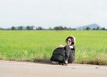 La mujer se sienta con la mochila que hace autostop a lo largo de un camino Fotografía de archivo libre de regalías