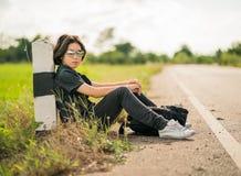 La mujer se sienta con la mochila que hace autostop a lo largo de un camino en campo Foto de archivo
