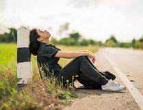 La mujer se sienta con la mochila que hace autostop a lo largo de un camino en campo Fotos de archivo