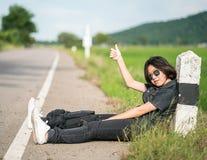 La mujer se sienta con la mochila que hace autostop a lo largo de un camino en campo Imágenes de archivo libres de regalías