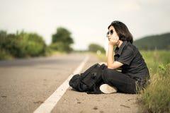 La mujer se sienta con la mochila que hace autostop a lo largo de un camino en campo Imagen de archivo