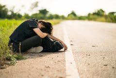 La mujer se sienta con la mochila que hace autostop a lo largo de un camino en campo Fotografía de archivo libre de regalías