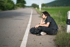 La mujer se sienta con la mochila que hace autostop a lo largo de un camino en campo Fotografía de archivo