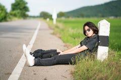 La mujer se sienta con la mochila que hace autostop a lo largo de un camino en campo Foto de archivo libre de regalías
