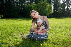 La mujer se sienta con una hija fotos de archivo libres de regalías