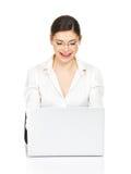 La mujer se sienta de la tabla con el ordenador portátil en la camisa blanca Foto de archivo libre de regalías