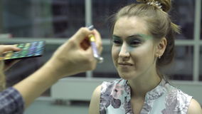 La mujer se sienta delante del visagiste, proceso del maquillaje almacen de video
