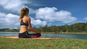 La mujer se sienta en actitud de la yoga en orilla del lago debajo del cielo