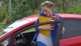 La mujer se sienta en coche y habla en el teléfono Después ella abre la puerta principal y sale del coche La muchacha sostiene la almacen de metraje de vídeo