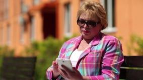 La mujer se sienta en el banco en patio y utiliza el smartphone blanco metrajes