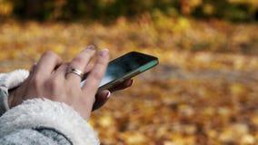 la mujer se sienta en el banco en parque de la ciudad y smartphone otoñales de las aplicaciones metrajes