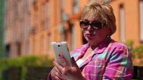La mujer se sienta en el banco y comunica vía smartphone metrajes