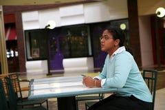 La mujer se sienta en el café Imagen de archivo libre de regalías