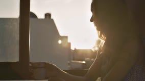 La mujer se sienta en el café de las bebidas del alféizar en la salida del sol