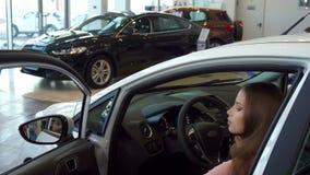 La mujer se sienta en el coche en la representación fotos de archivo