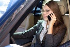 La mujer se sienta en el coche y habla por el teléfono Fotos de archivo