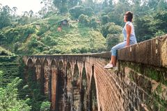 La mujer se sienta en el Demodara que nueve arcos tienden un puente sobre el s visitado Fotografía de archivo