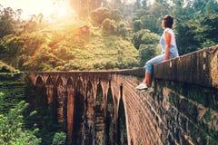 La mujer se sienta en el Demodara que nueve arcos tienden un puente sobre el s visitado Foto de archivo