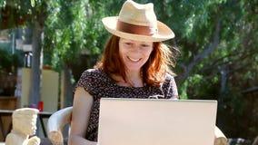 La mujer se sienta en el jardín que disfruta de una conversación en su ordenador portátil en el sol almacen de video